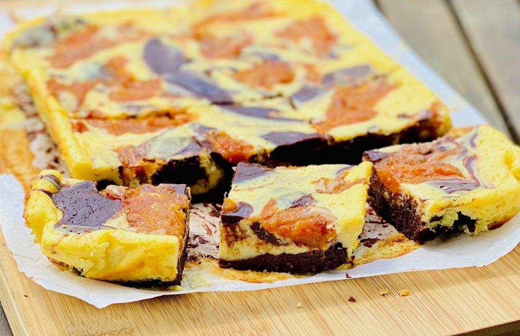 Brownie Cheesecake aufgeschnitten auf einem Holzbrett