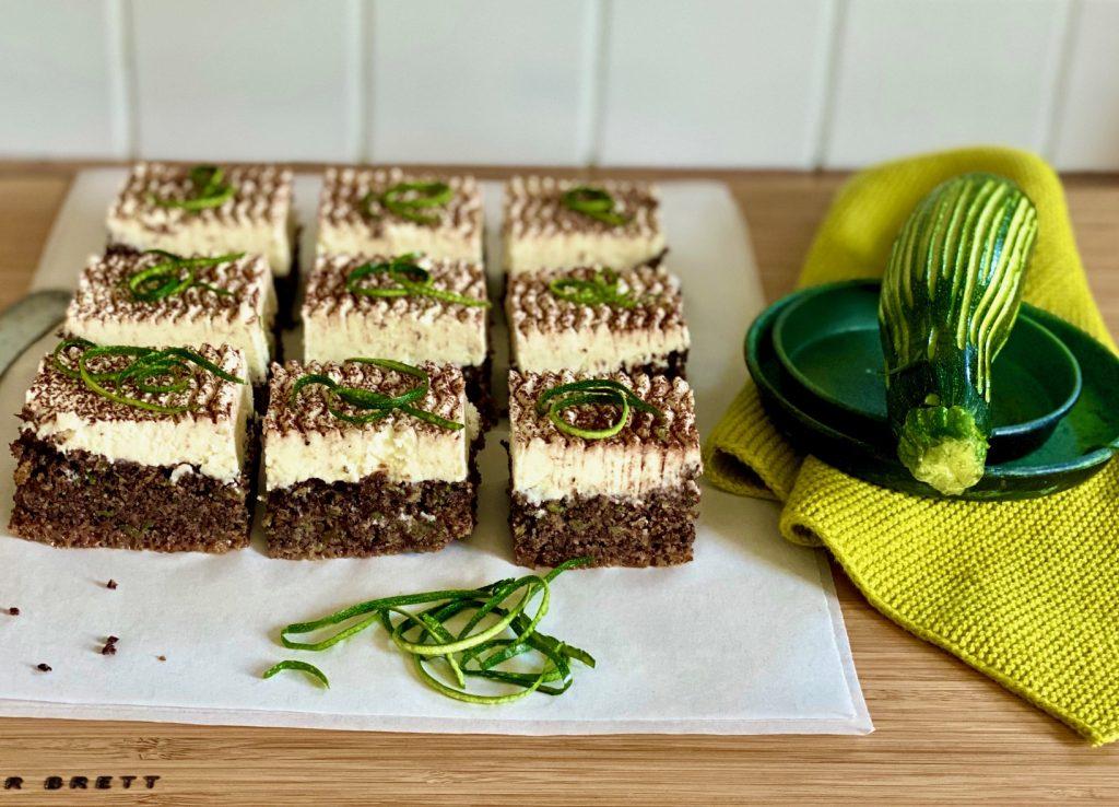 Zucchinikuchen mit Schokolade, Mohn und Rapsöl, aufgeschnitten, daneben eine Zucchini