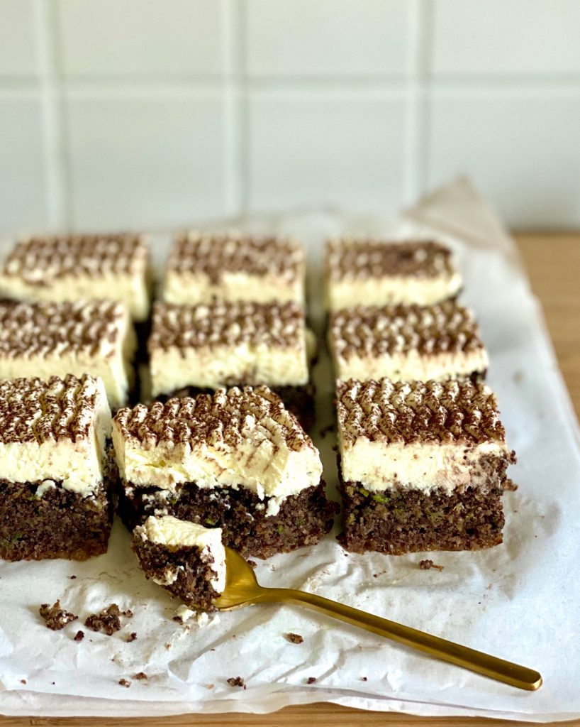 Zucchinikuchen mit Schokolade, Mohn und Rapsöl, ein Stück angegessen mit einem goldenen Löffel