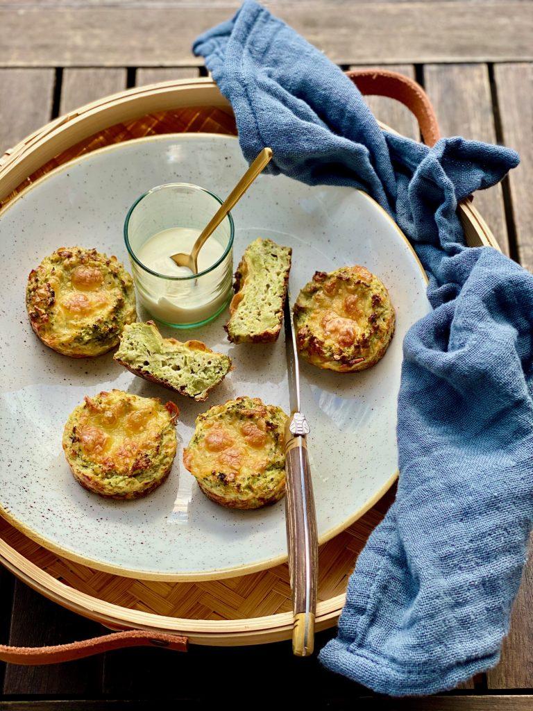 Brokkoli-Muffins auf einem Steingutteller, eines ist aufgeschnitten