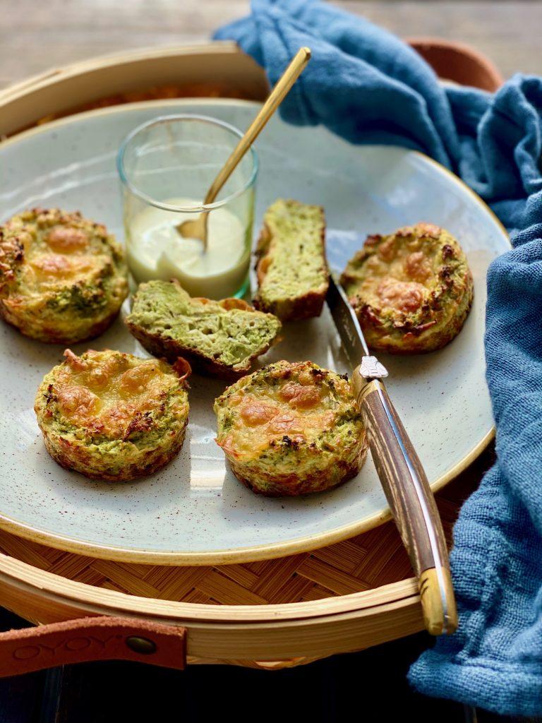 Brokkoli-Muffins Nahaufnahme, eines aufgeschnitten, daneben ein Messer und eine blaue Stoffserviette