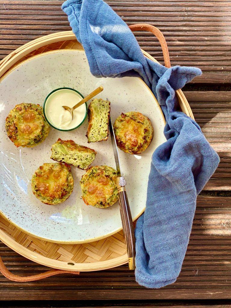 Brokkoli-Muffins auf einem Steingutteller, der in einem Stroh-Tablett steht
