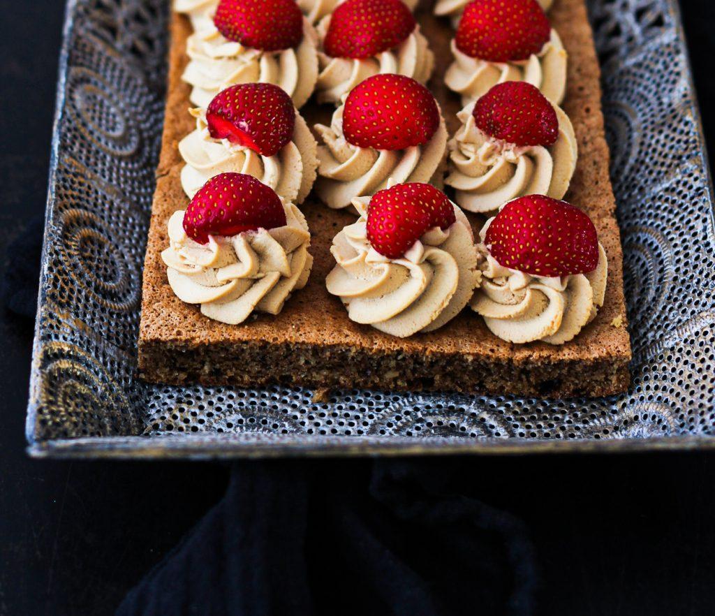Dunkler Biskuit mit Creme und Erdbeeren auf einem orientalischen silbernen Tablett