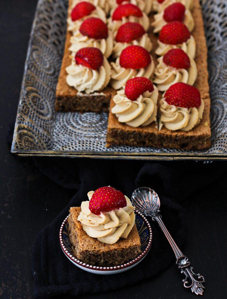 Dunkler Biskuit mit Creme und Erdbeeren auf einem orientalischen silbernen Tablett, davor in kleiner Stückchen auf einem  kleinen runden orientalsichen Tellerchen
