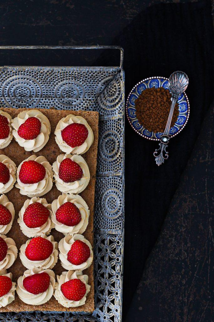 Dunkler Biskuit mit Creme und Erdbeeren auf einem orientalischen silbernen Tablett von oben fotografiert, daneben Kaffeegranulat