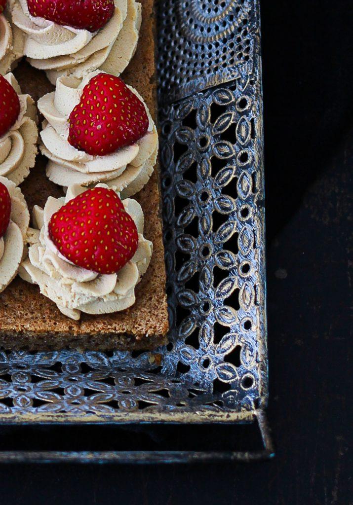 Dunkler Biskuit mit Creme und Erdbeeren auf einem orientalischen silbernen Tablett, Nahaufnahme von oben