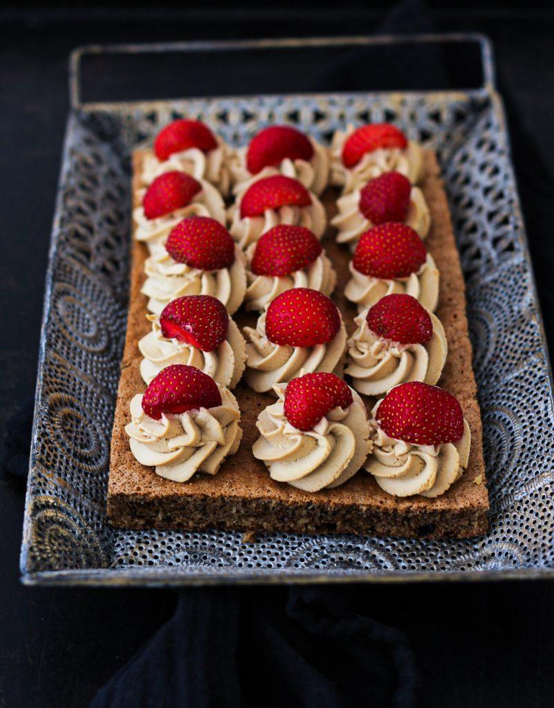 Dunkler Nuss-Biskuit mit Creme und Erdbeeren auf einem orientalischen silbernen Tablett