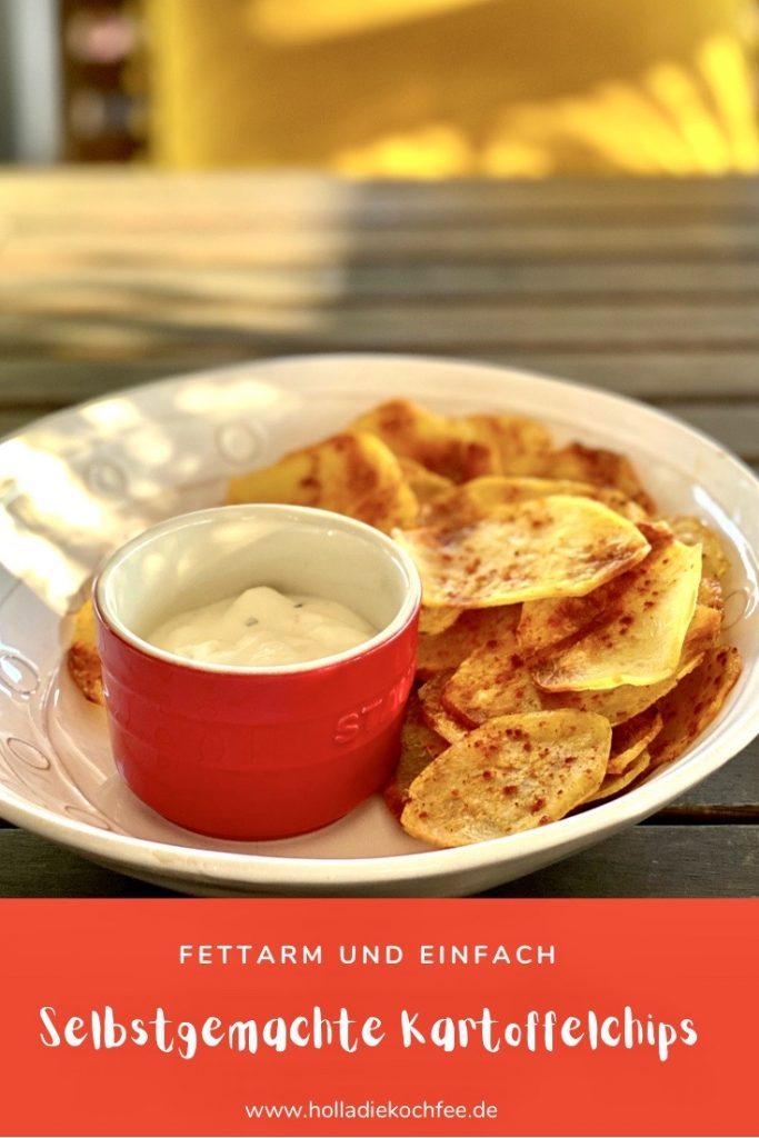 Selbstgemachte fettarme Kartoffelchips auf einem hellen Teller, mit einem Dip im roten Schälchen daneben. Vorlage für Pinterest.
