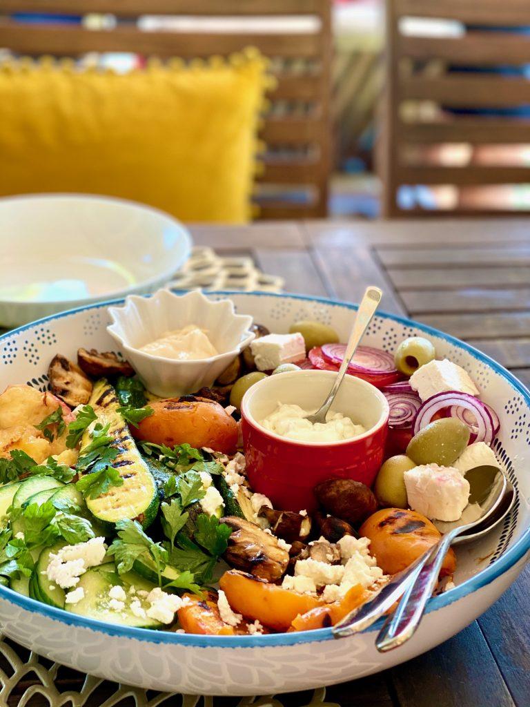 Bunter Somersault mit Aprikosen und Schafskäse in einer großen Schüssel auf einem Gartentisch