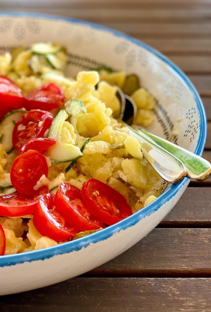 Kartoffelsalat light mit Tomaten und Gurken fertig angemacht in einer bunten großen Schale