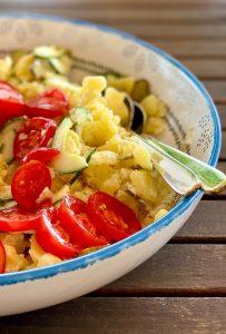 Kartoffelsalat mit Tomaten und Gurken in einer großen Schüssel