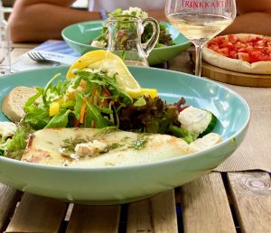 Bunter Salat, darauf eine Tintenfischtube vom Grill