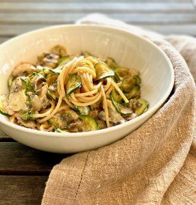 Vollkornspaghetti mit Zucchini und Pilzen in einem tiefen Teller