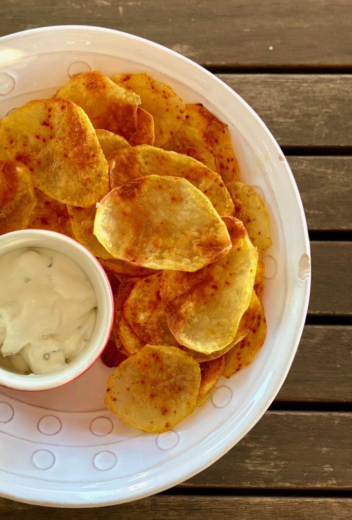 Selbstgemachte fettarme Kartoffelchips auf einem hellen Teller, mit einem Dip im roten Schälchen daneben, von oben fotografiert
