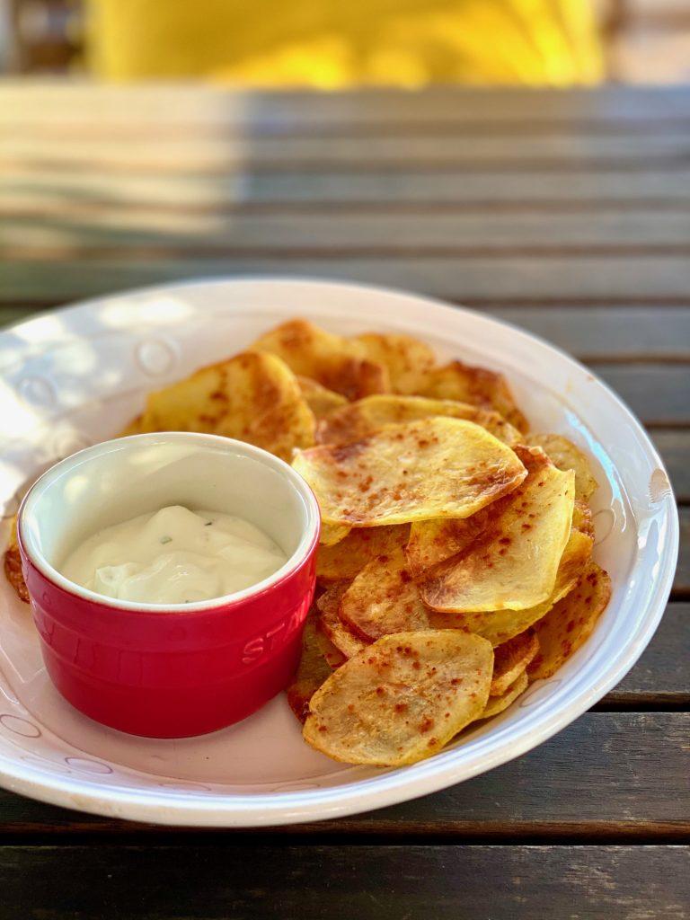 Selbstgemachte fettarme Kartoffelchips auf einem hellen Teller, mit einem Dip im roten Schälchen daneben