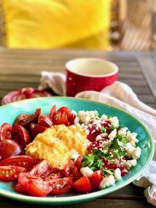Auf einem türkisen Teller sind Rühreier, Tomaten und Schafskäse