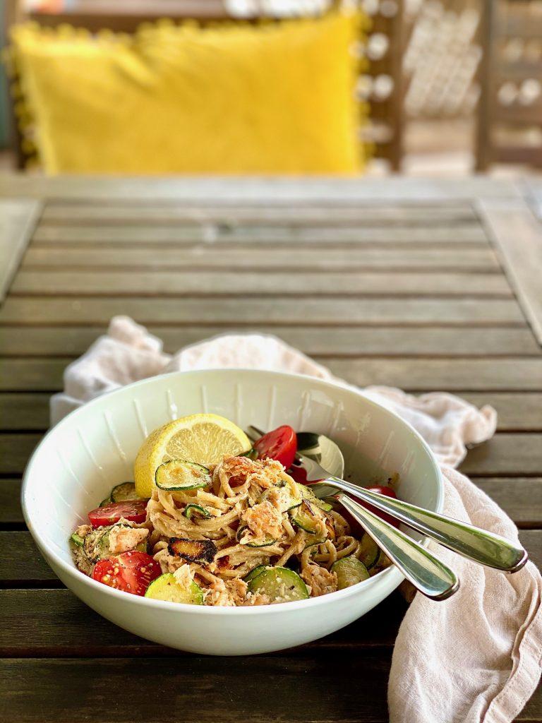 Ein Teller Pulled Lachs Pasta auf einem Gartentisch aus Holz