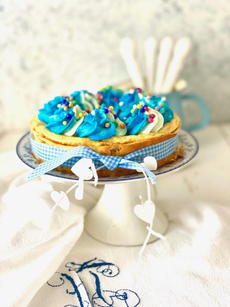 Cheesecake mit blauem Tapping und Zuckerperlen auf einem weißen Tortenständer v