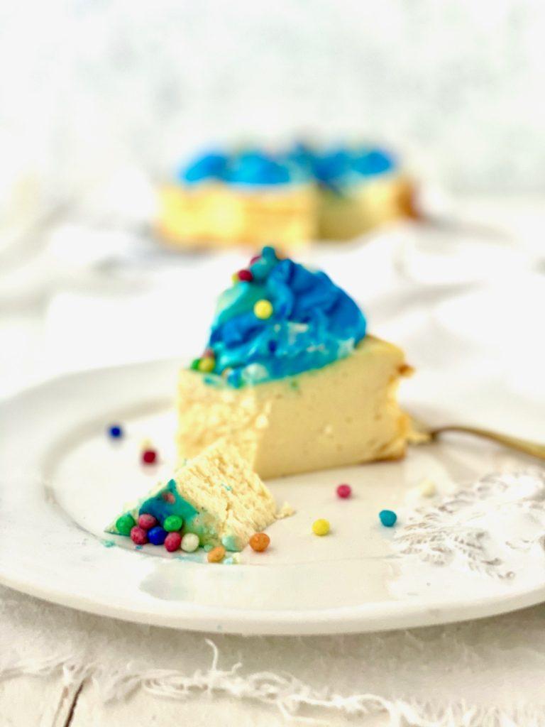 Cheesecake mit blauem Tapping und Zuckerperlen, ein Stück abgeschnitten