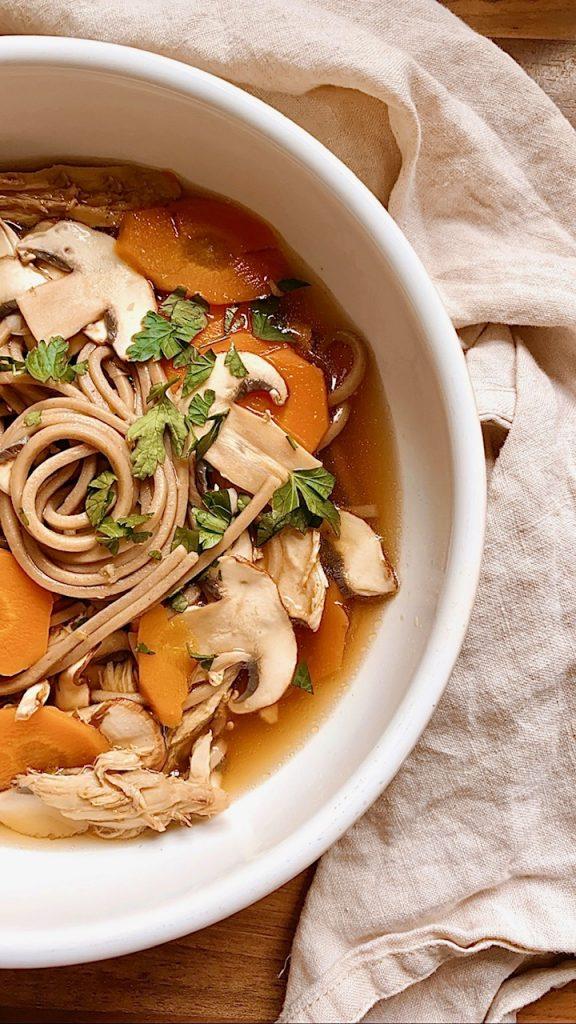 Schnelle Misosuppe mit Sobanudeln, Karotten und Champignons in einem weißen Teller von oben fotografiert