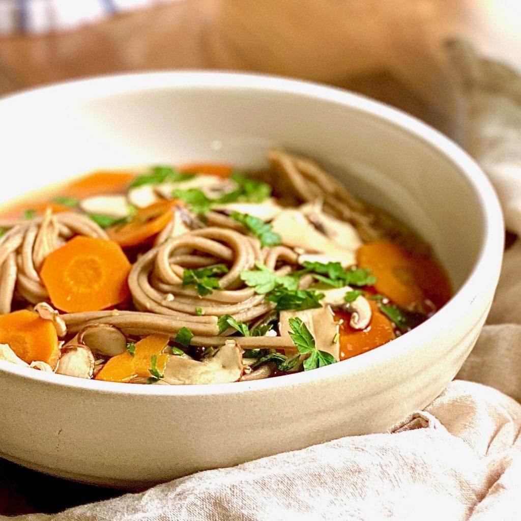 Schnelle Misosuppe mit Sobanudeln, Karotten und Champignons in einem weißen Teller