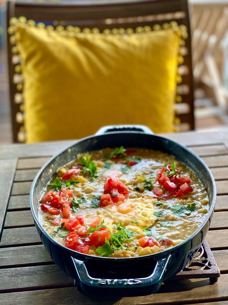 Kartoffel-Linsen-Shakshuka mit frischen Tomaten auf einem Gartentisch