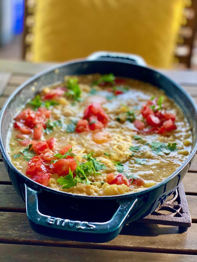 Kartoffel-Linsen-Shakshuka mit frischen Tomaten in einem Bräter