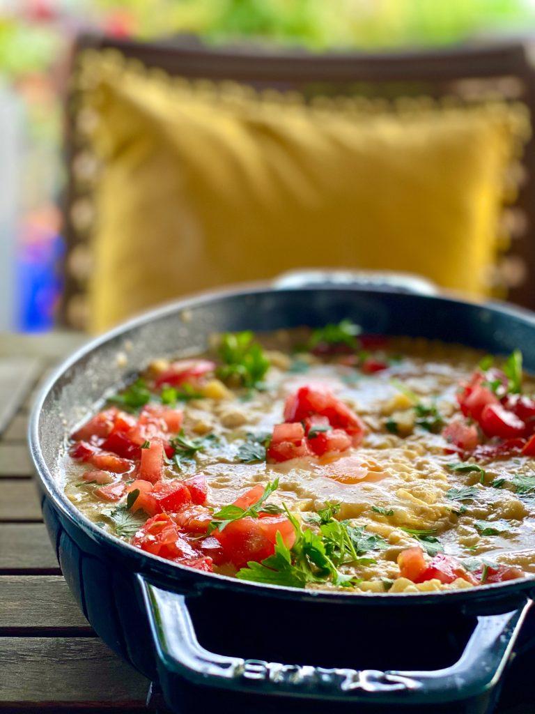 Kartoffel-Linsen-Shakshuka mit Eiern und frischen Tomaten im Bräter