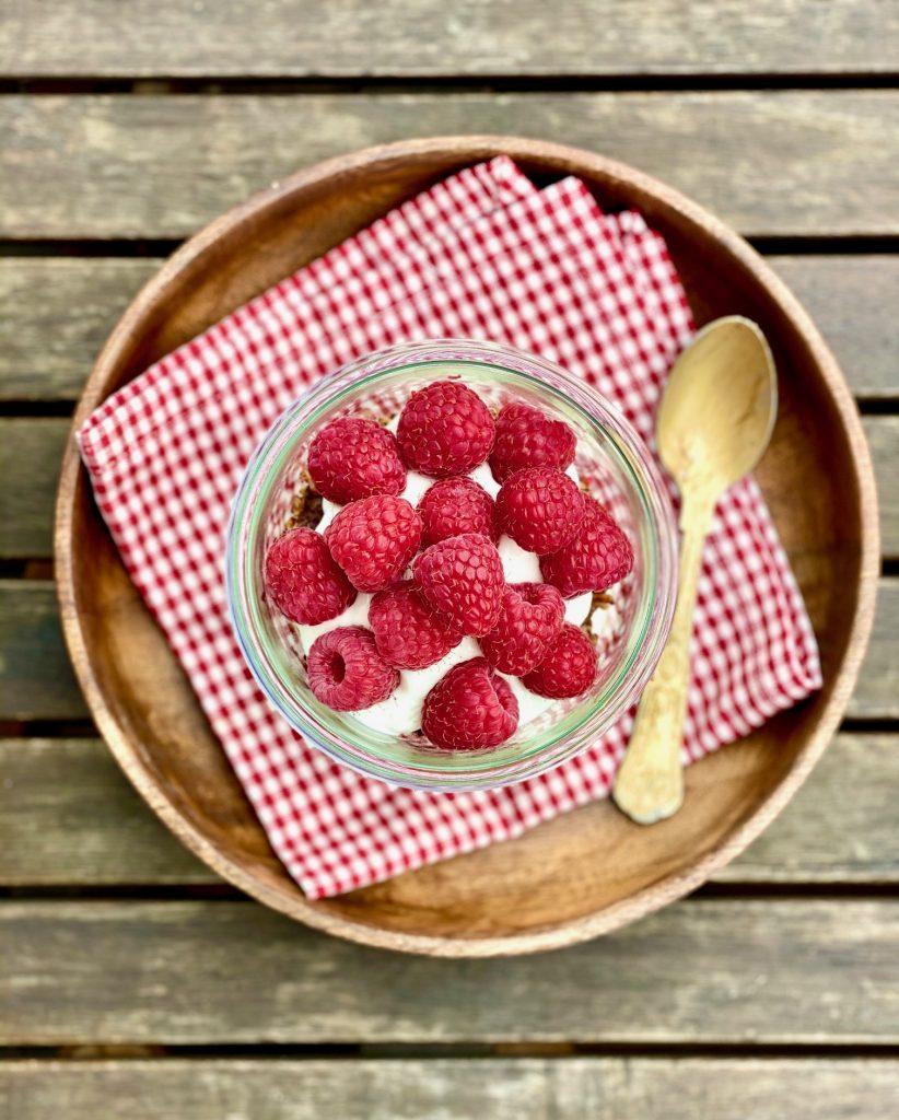 Schichtdessert mit Schoko-Haferflocken-Crunch. Auf einem Holzteller von oben fotografiert