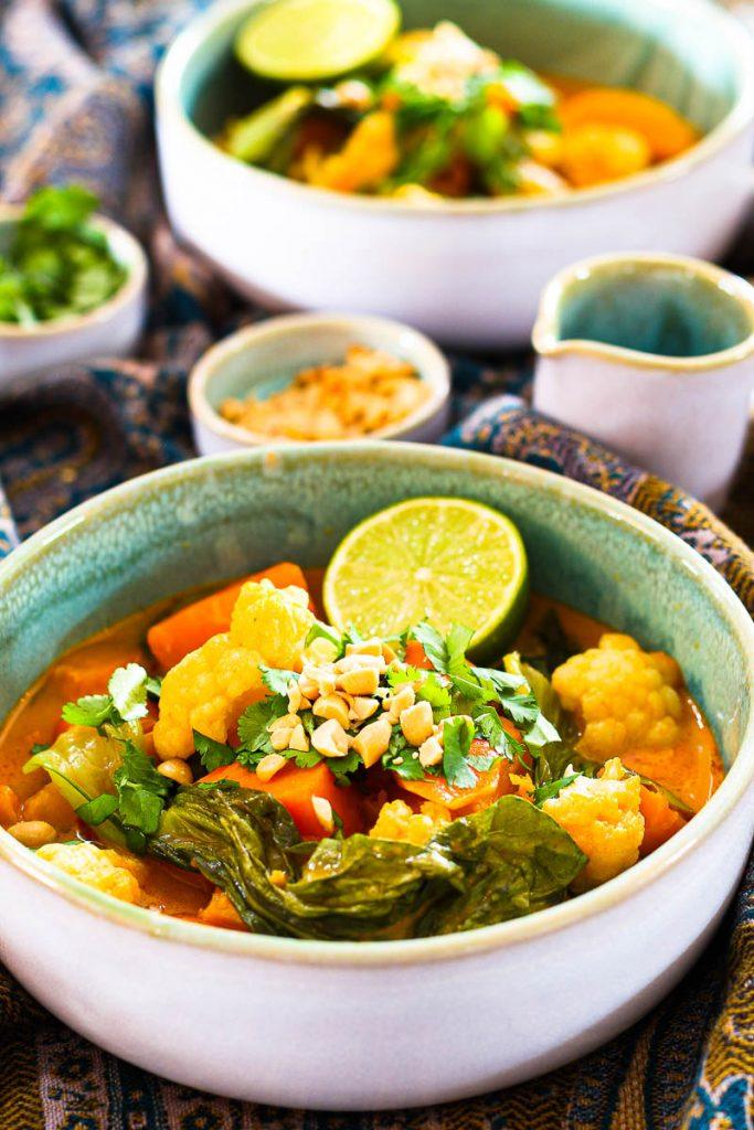 Veganes Butternut-Süßkartoffel-Curry angerichtet mit Koriander und Erdnüssen