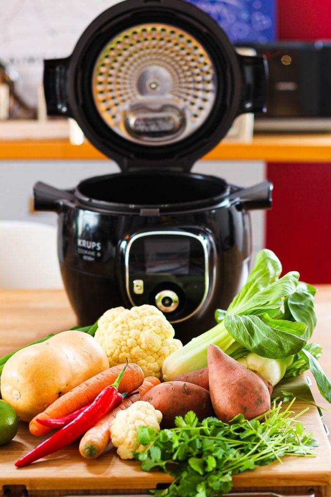Veganes Butternut Süßkartoffel Curry aus der Cook4me. Das Gerät in Schwarz, davor Gemüse auf einem Brett