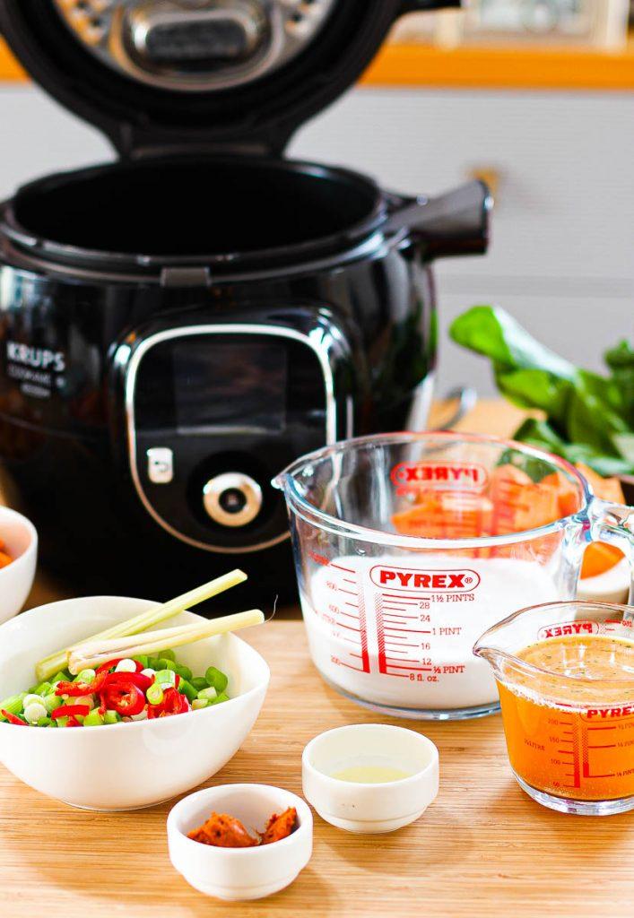 Cook4me offen, davor Kokosmilch und Brühe in Messbechern