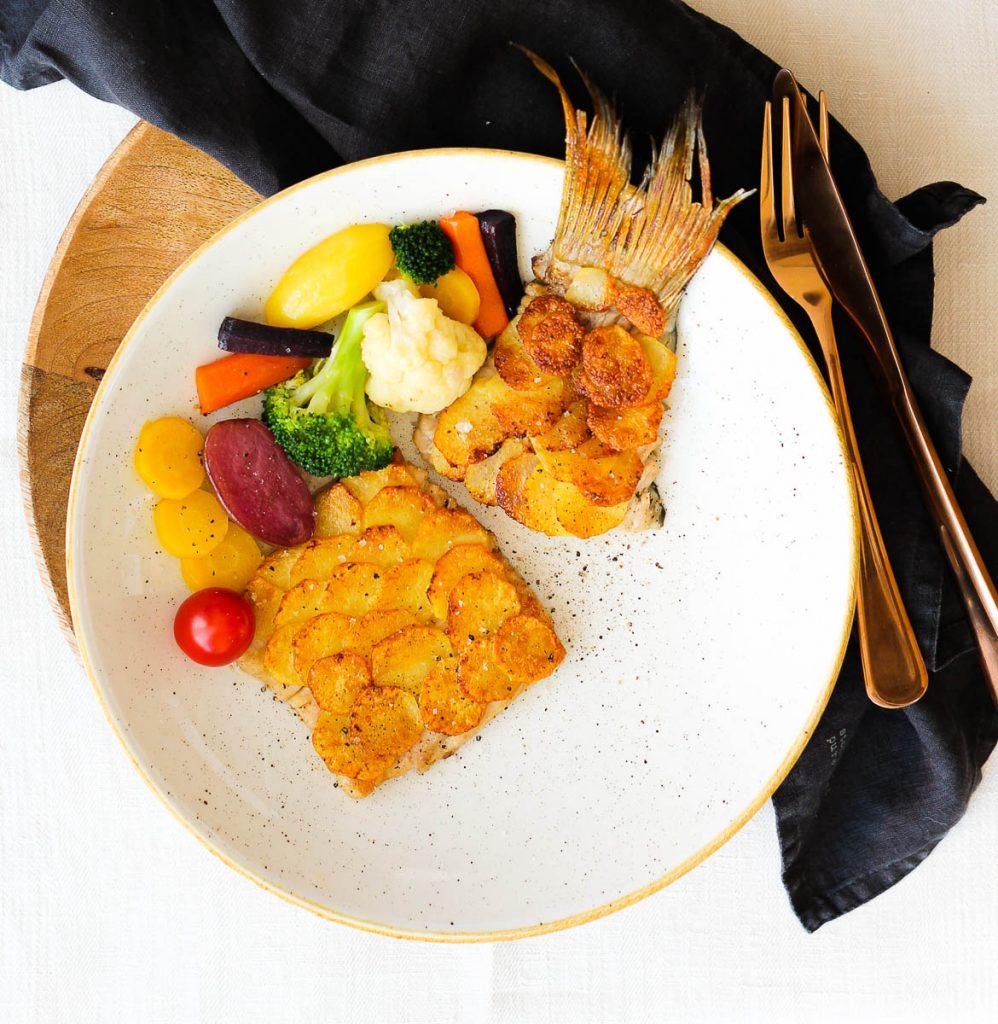 Karpfenfilet mit Kartoffelschuppen von oben, daneben kupferfarbenes Besteck und ein schwarzes Leinentuch