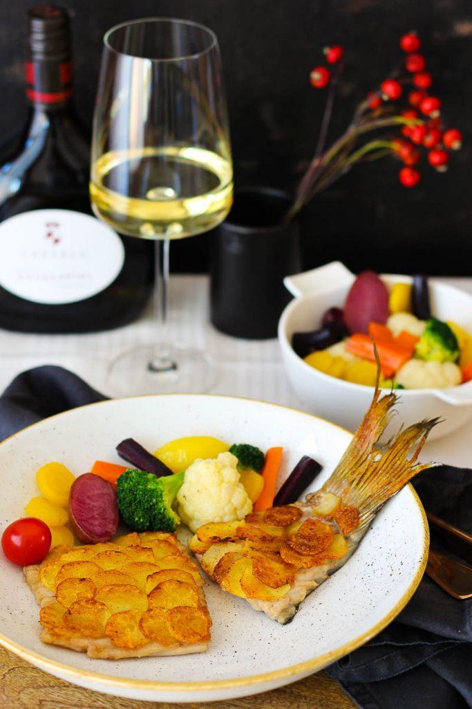 Karpfenfilet mit Kartoffelschuppen, im Hintergrund Frankenwein