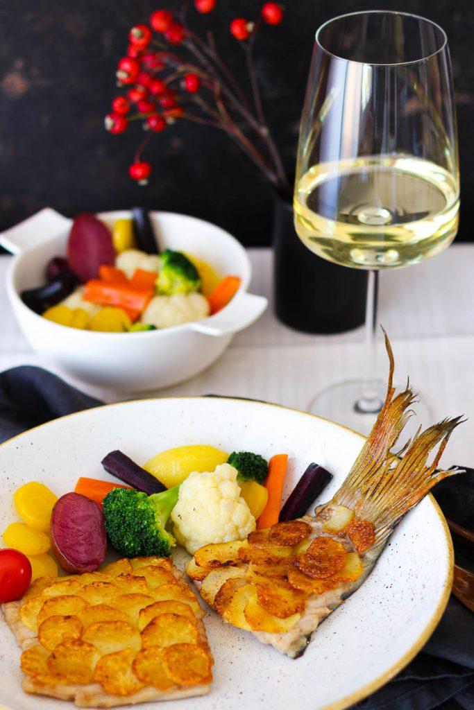 Karpfenfilet mit Kartoffelschuppen und Silvanerbutter, auf einer Leinentischdecke mit einem Glas Silvaner