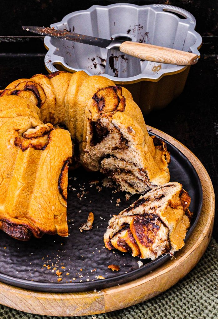 Saftiger Nutella Gugelhupf, ein Stück aufgeschnitten, dahinter die leere Form