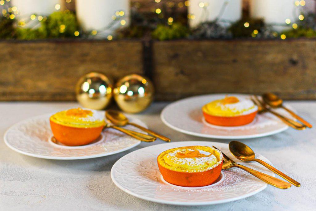 Orangen Cheesecakes in Orangen gebacken vor einem Weihnachtsgesteck