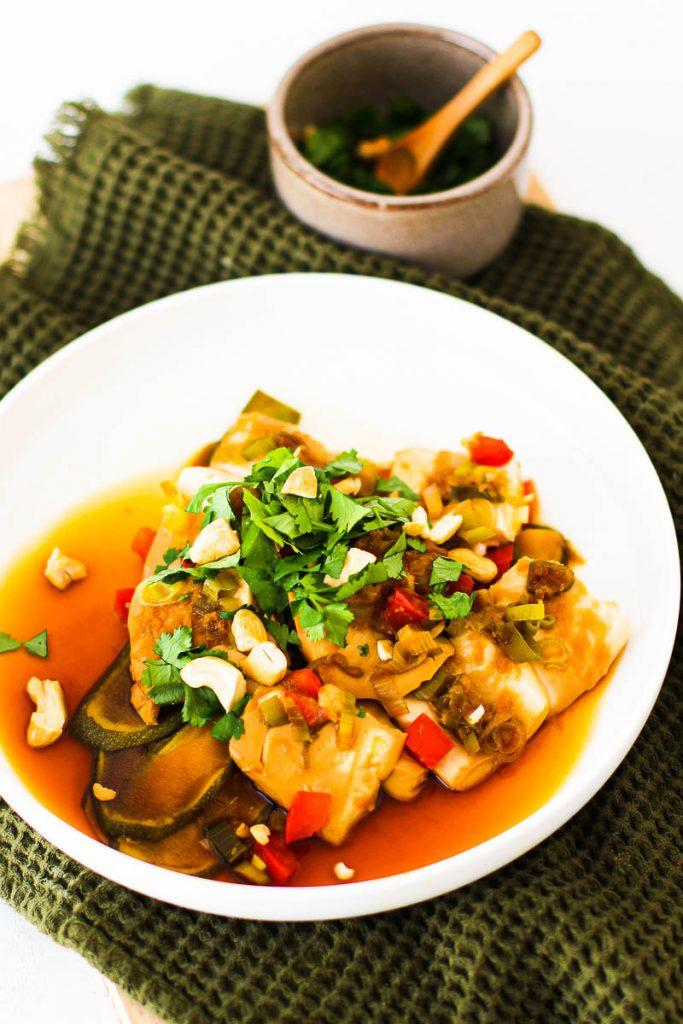 Asiagemüse mit Tofu angerichtet auf einem weißen Teller mit Koriander und Nüssen