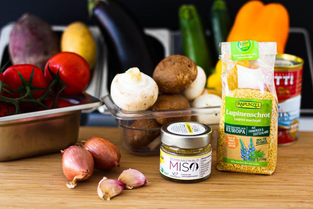 """Zutaten für veganes Ratatouille aus dem Ofen mit Lupinen-""""Parmesan"""" auf einem Holzbrett"""