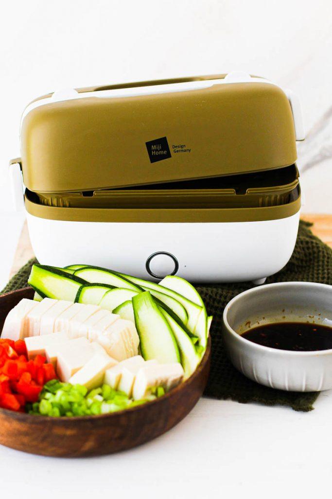 Miji Cooking Box One, davor eine Holzschale mit Zucchini, Tofu, Paprika und Frühlingszwiebeln