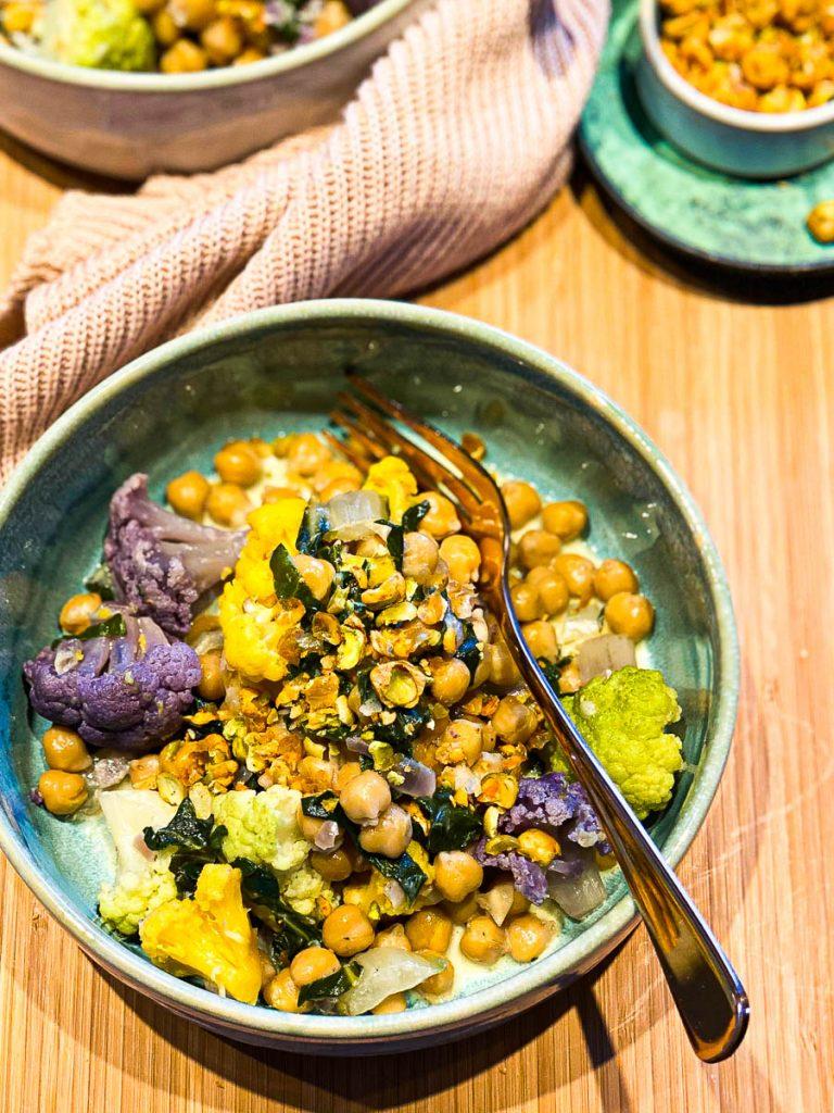 Cremiger Kichererbsen Eintopf mit Mangold und Blumenkohl auf einem Brett in zwei Schüsseln