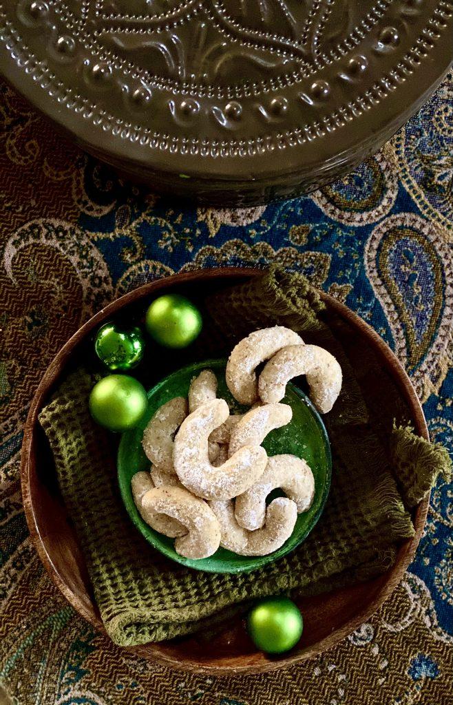 Vanillekipferl in einer Holzschale mit kleinen grünen Kugeln