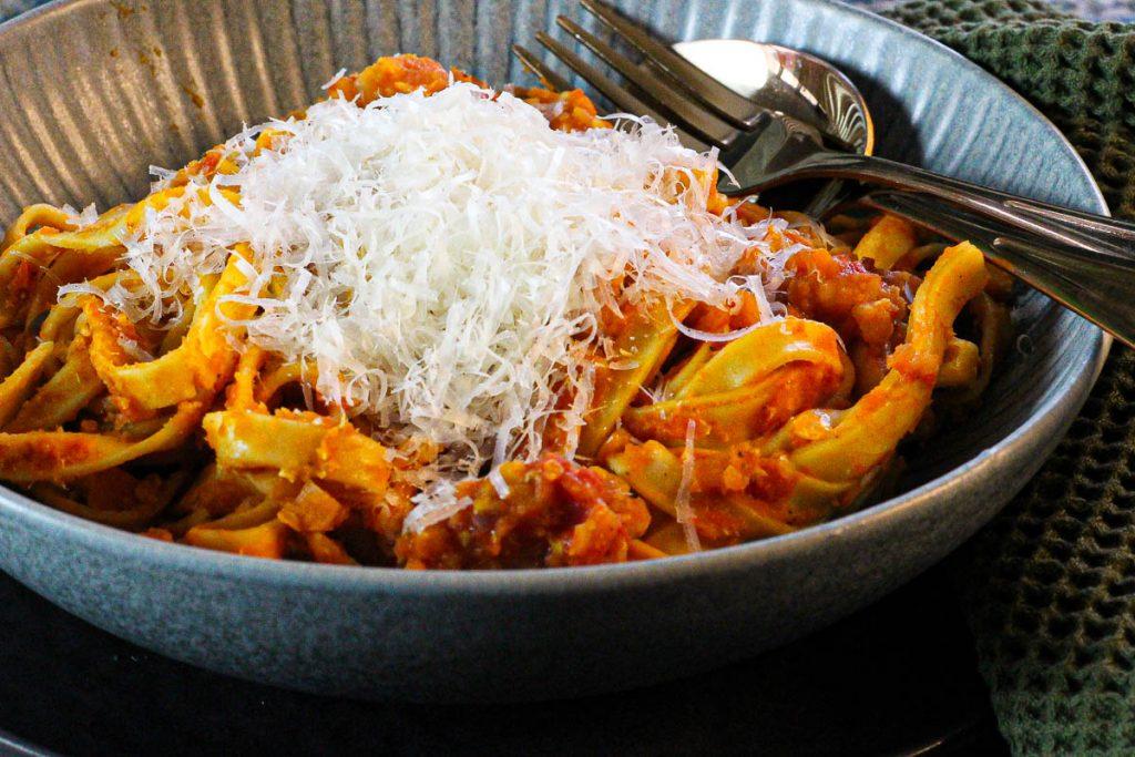 One Pot Pasta mit Linsenbolognese, angerichtet mit Parmesan in Nahaufnahme