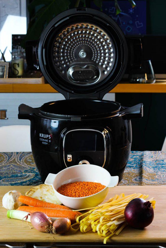 Zutaten für die One Pot Pasta mit Linsenbolognese, dahinter das Gerät aufgeklappt