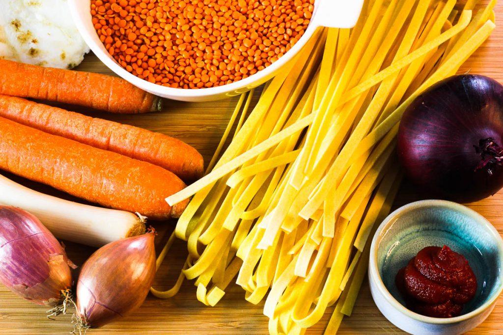 Zutaten für die One Pot Pasta mit Linsenbolognese auf einem Brett