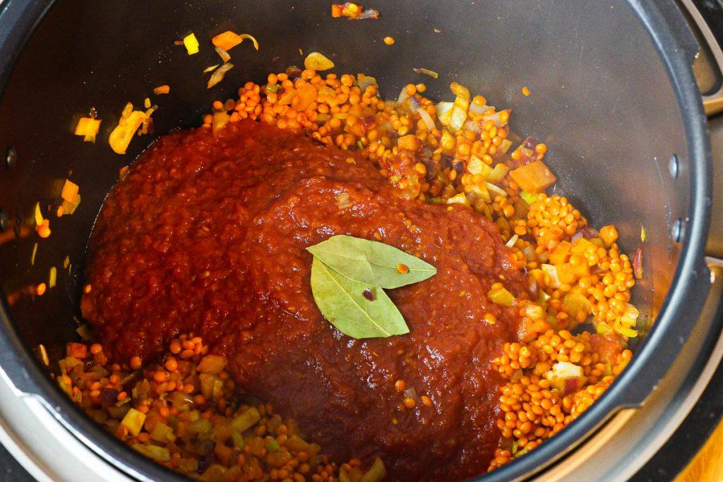 Linsen und Tomaten kommen in den Topf