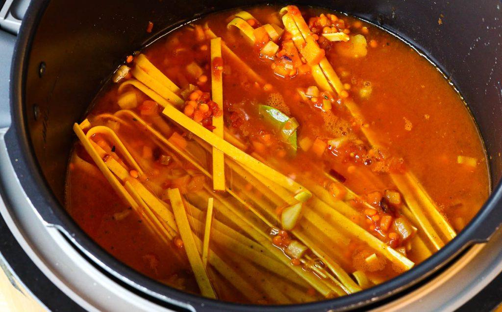 Nudeln und Brühe für die One Pot Pasta mit Linsenbolognese kommen in den Topf