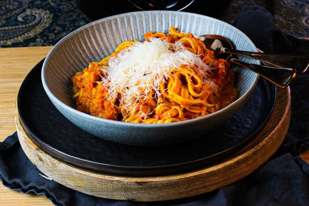 One Pot Pasta mit Linsenbolognese in einem grauen Steingut Teller