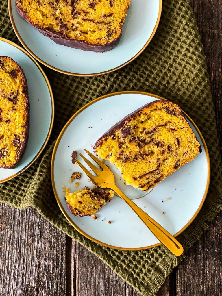 Weltbester Eierlikörkuchen mit Schokolade, aufgeschnitten auf blauen Desserttellern -ein Stück angegessen