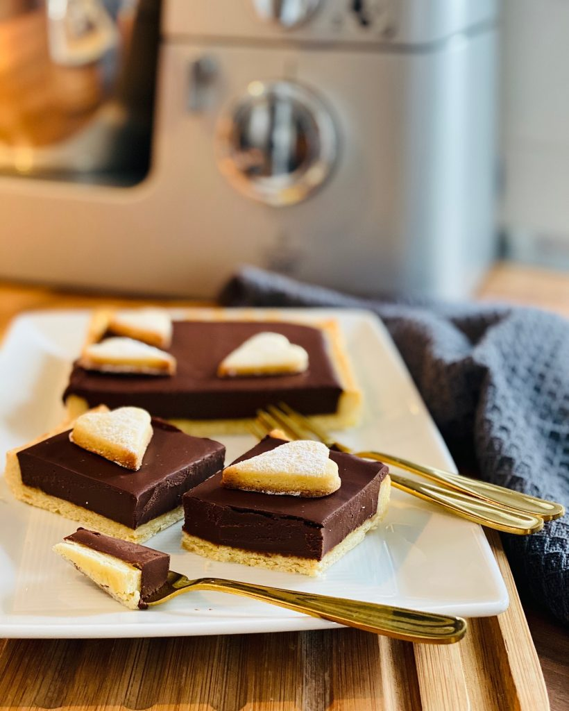 Weltbeste Schokoladentarte aufgeschnitten vor der Küchenmaschine